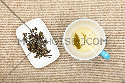 Big empty cup of green tea with leaf on bottom and white plate with dried green tea leaves on flax canvas tablecloth, close up, elevated top view, directly above