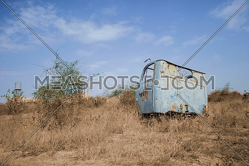 an abandoned front part of a truck in the middle of a field