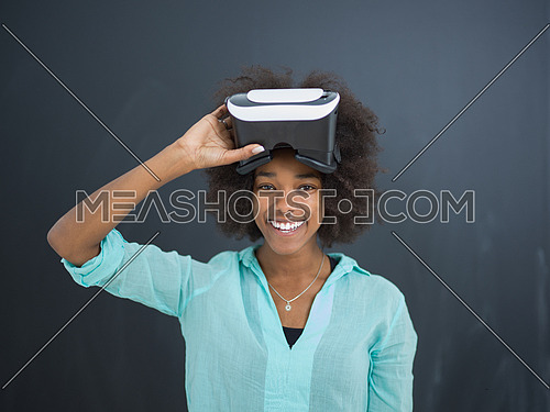 Happy african american girl getting experience using VR headset glasses of virtual reality, isolated on gray background