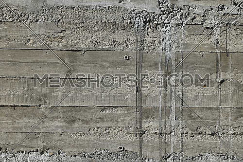 Concrete wall with wooden pattern impress from wooden form board shuttering and with sags of cement