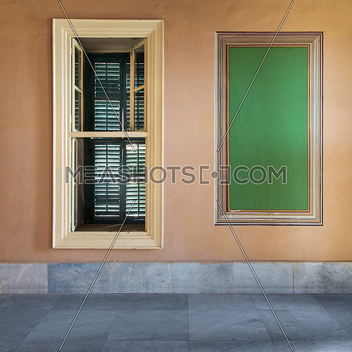 Beautiful elegant rectangular green frame with ornate border and narrow window with closed green shutter on orange wall with white marble floor, in abandoned old building