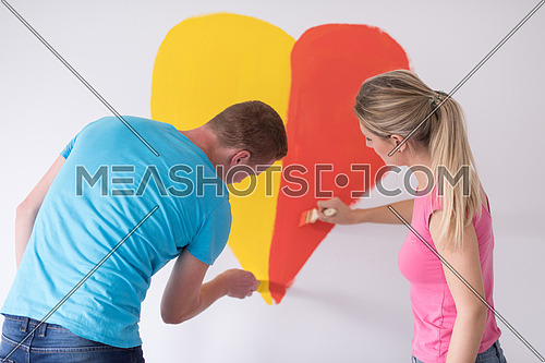 Young happy couple are painting a heart on the wall while doing repair at home.