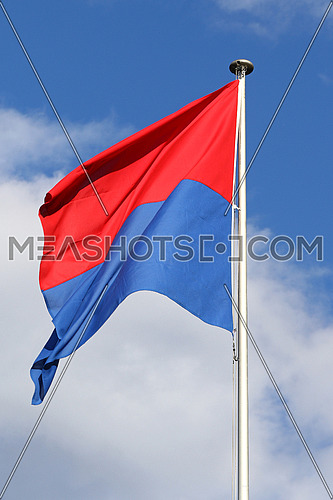 Flag of the State and Republic of Canton Ticino, Switzerland, flapping in the wind against blue skies