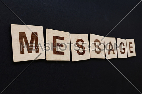 Close up word MESSAGE on wooden letter signs over black board background