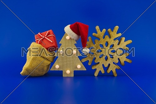 Stylized wooden Christmas tree with red Santa hat and jute sack with gift boxes on a festive blue background. New Year and Christmas gift season concept