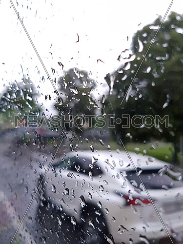 White SUV vehicle driving in city traffic in the rain from behind a glass covered in raindrops