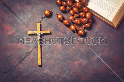Big wooden Rosary beads and crucifix cross with jesus and bible book,spiritual atmosphere ,religion concept.