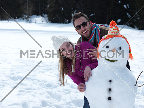 portrait of happy young couple with snowman at beautiful winter day with fresh snow and forest in background