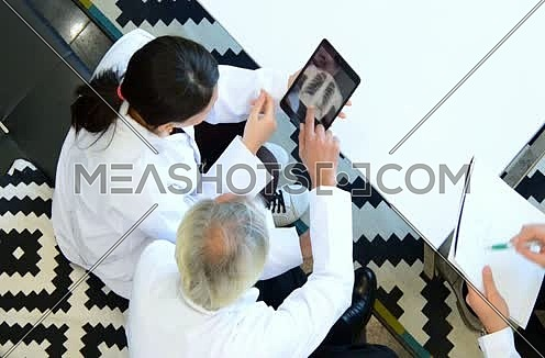 top shot -  middle eastern doctors discussing x-ray on tablet