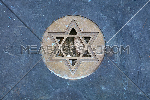 Metal Star of David (Magen David) Jewish symbol at gravestone, close up