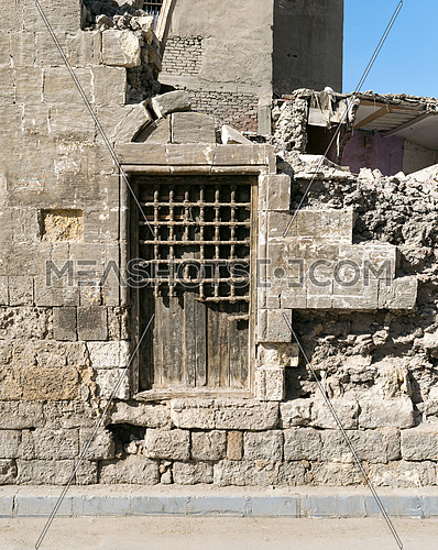 Old abandoned wall with one closed wooden window covered by broken wooden iron grid, El-Dard El-Ahmar, Cairo, Egypt
