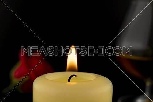 Single burning yellow candle in front of a glass of Cognac or Brandy and red roses against dark background