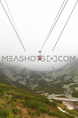 Red mountain cableway car lift in clouds and fog, low angle view