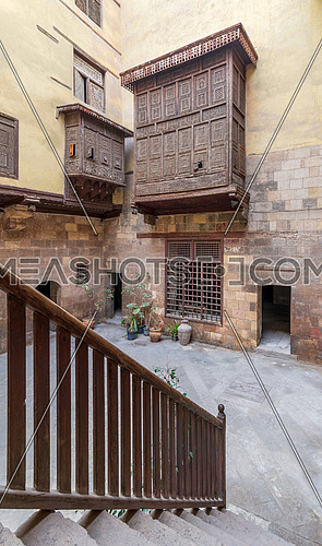 Staircase with wooden balustrade revealing facade of ottoman era historic house of El Sehemy with wooden oriel windows - Mashrabiya - located at Moez Street, Cairo, Egypt