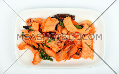 Seafood calamari squid, seaweeds and chili marinated salad snack with souse on white dish plate over white background, top view