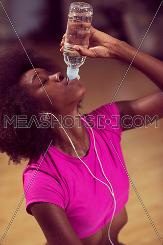 young afro american woman in gym on pilates workout break teaking breath and fresh drinking  water