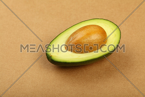 One fresh ripe green avocado half with pit stone on natural brown kraft paper background, detail, close up, elevated top view, high angle view