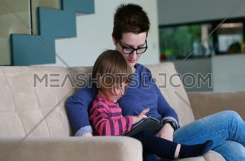 Mother teaches daighter how to use digital tablet