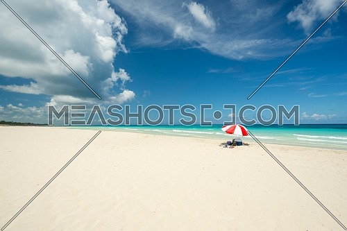 Beautiful beach of Varadero during a sunny day, fine white sand and turquoise and green Caribbean sea,on the right one red parasol,Cuba.concept photo,copy space.