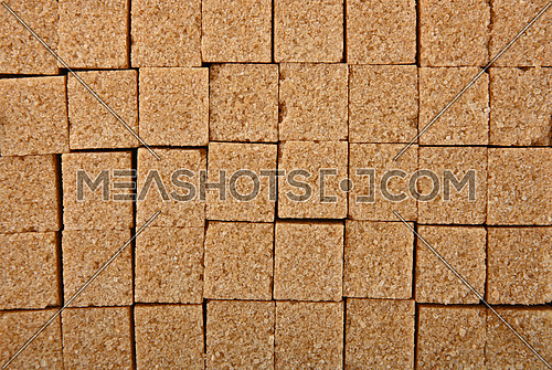 Close up background texture pattern of brown cane sugar cubes arranged