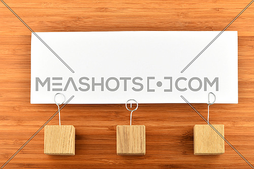 Together, one big white paper note with three wooden holders on wooden bamboo background for presentation