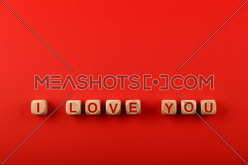 Wooden cube signs with I LOVE YOU words over red background and copy space, elevated top view, directly above