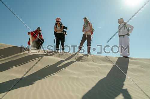 Group of tourists walking on sands with bedouin guide while exploring Sinai Trail from Ain Hodouda by day.