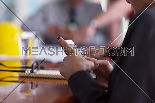 close up of  businesswoman hands  using smart phone and laptop computer, people group in office meeting  room blurred in backgronud