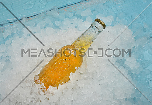 Close up one clear glass bottle of cold lager beer on crushed ice at retail display, elevated high angle view