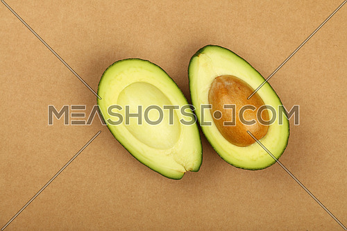 One fresh ripe green avocado cut to two hallves with pit stone on natural brown kraft paper parchment background, detail, close up, elevated top view