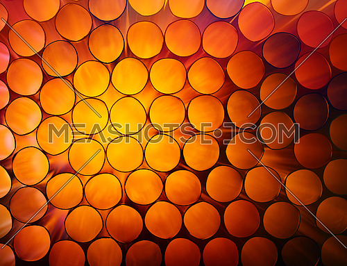 Abstract warm red and orange toned vivid colorful background texture of backlit stack drinking straw circles