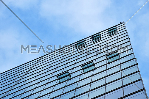 Background texture of modern business skyscraper building glass windows pattern with reflection over cloudy blue sky, low angle view