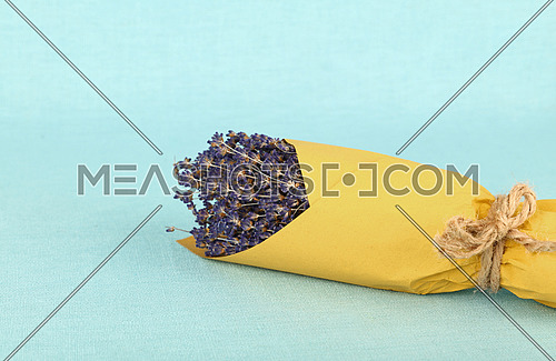 Close up bouquet of dried lavender flowers wrapped in yellow paper on blue tablecloth, high angle view