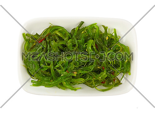 Close up portion of green wakame seaweed salad on white plate isolated on white background, elevated top view, directly above