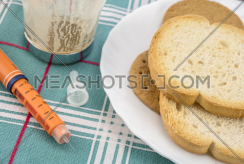 Medication during breakfast, injector of insulin together with a bottle of pills, conceptual image, composition horizontal