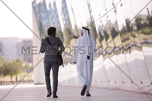 arabian  business people  walking in front of modern corporate building