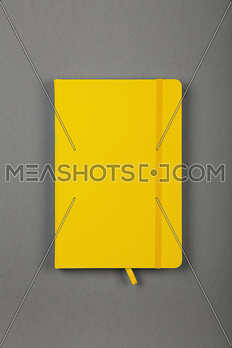 One closed yellow faux leather cover notebook on grey paper background, flat lay, directly above