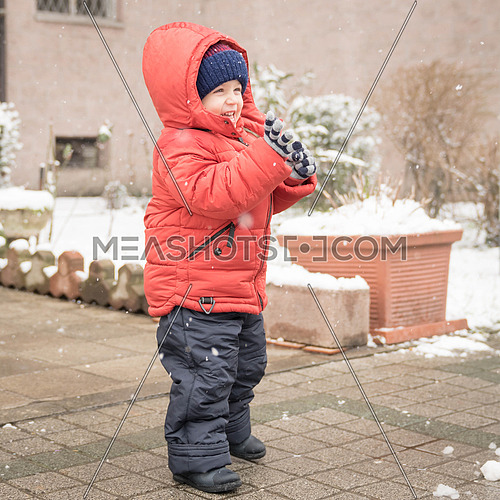 Infant boy smiles cheerfully while it's snowing,dressed in a red winter jacket and a woolen hat.