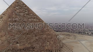 Reveal Shot for The Great Pyramid of Khufu (Cheops) and the top of Menkaure Pyramid at Great Pyramids of Giza Area in Cairo by day.