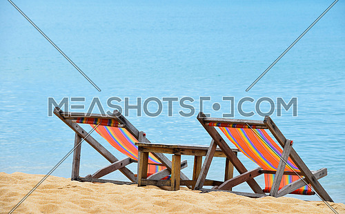 Two empty colorful canvas lounge sling chairs and wooden table over blue sea, on sand beach of resort in Thailand, rear view, high angle