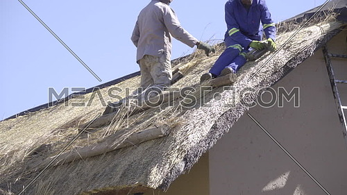View of African construction workers fixing roof