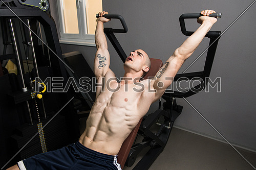 Young Bodybuilder Doing Heavy Weight Exercise For Shoulders On Machine