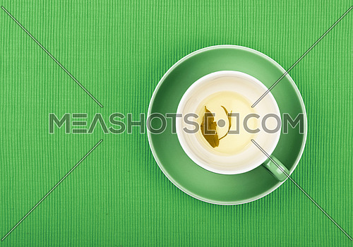 Empty cup of clear green tea with leaf on bottom at saucer over green textile tablecloth, close up, elevated top view