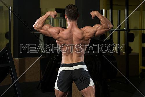 Serious Man Standing Strong In The Gym And Flexing Muscles