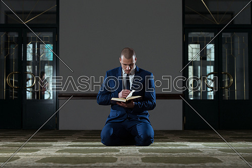 Muslim Businessman Reading Holy Islamic Book Koran In The Mosque