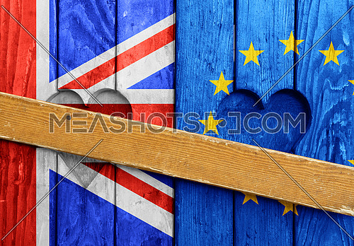 Close up closed wooden window shutters with heart shapes, UK and EU flags painted as symbol of Brexit