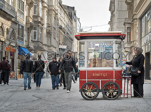 Istanbul, Turkey - April 24, 2017: Old Turkish lady buying fast food meal from a traditional Turkish Simit (Turkish Bagel) cart in Istiklal street and people walking at afternoon