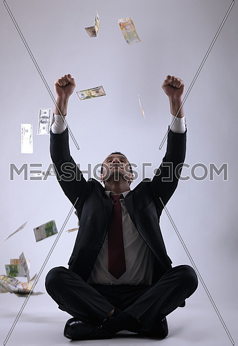 Portrait of a business man holding and catch falling money bills, isolated on white background in studio