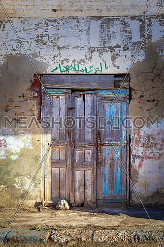 Closed wooden weathered door and shabby old grunge stone wall on abandoned district. Arabic text above door says: For Rent