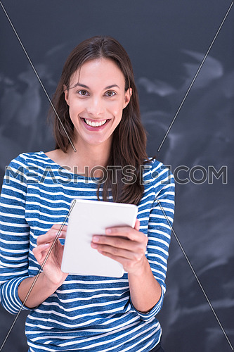 Happy young woman using tablet computer in front of chalk drawing board